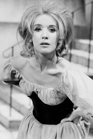 La comédienne porte une robe dans un décor de théâtre.