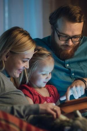 Une mère et un père regardent une tablette avec leur fille.