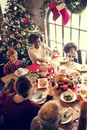 Une famille et des amis réunis autour d'une dinde du temps des Fêtes.