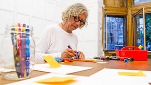 L'artiste Hervé Tullet bricole avec un feutre bleu.
