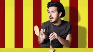 L'animateur Sébastien Diaz, photographié sur un fond ligné jaune et rouge, s'amuse avec de petits pains.