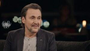 Guy A. Lepage est assis sur un canapé dans le studio de l'émission « Pour emporter ».