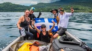 L'athlète Normand Jr Piché est accompagné de quelques membres de son équipe sur un bateau. Ils ont un drapeau du Québec avec eux.