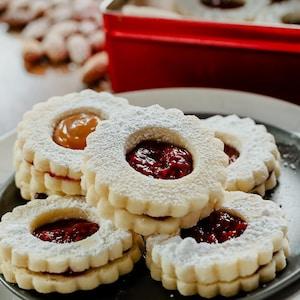 Des biscuits miroirs à la confiture de framboises sur un plateau de service.