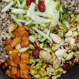 Bol de quinoa tricolore comprenant des noix de grenoble, des graines de citrouille, des amandes, des canneberges, des champignons, du fenouil, et des cubes de citrouilles.