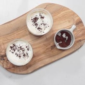 Deux bols de café sont sur une planche de bois.