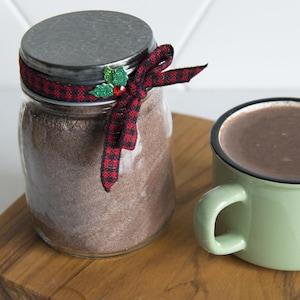 Une tasse de chocolat chaud est à côté d'un pot en verre rempli de poudre de chocolat.