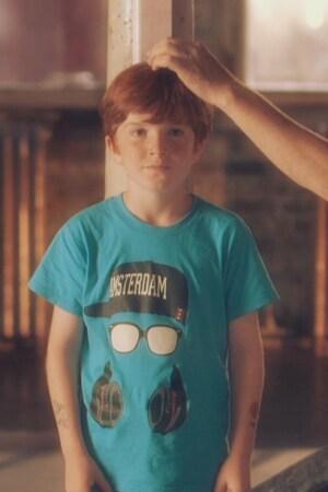 Un enfant se tient droit sur un mur où un homme trace une ligne pour marquer sa grandeur.