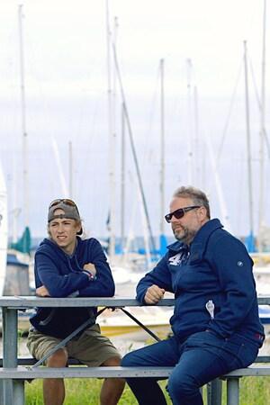 Ils sont assis à une table de pique-nique, aux abords d'une marina