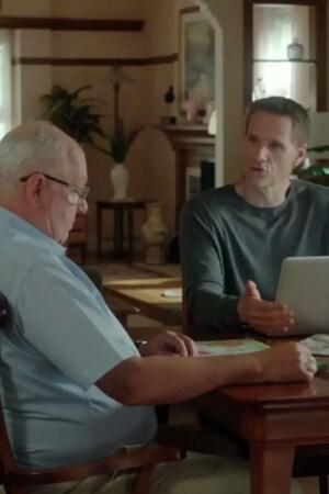À la table de la salle à manger, Jean-Pierre lit son journal et François écrit à l'ordinateur.