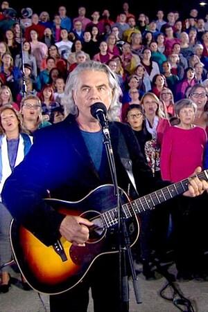 Richard Séguin, à la guitare chante. Derrière lui, une immense chorale de 600 choristes.