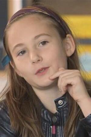 Une fillette à l'école primaire porte un bandeau et une veste de cuir.