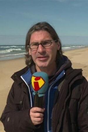 Il tient un micro devant lui sur une plage.