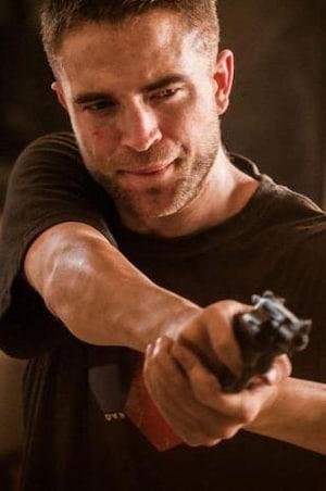 Un jeune homme pointe son arme