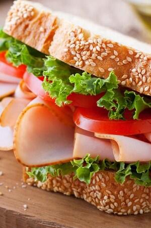Un sandwich à la dinde avec des tranches de tomates et de la laitue.