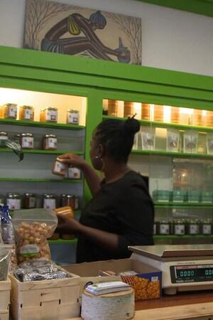 Une femme place des produits derrière un comptoir d'épicerie.