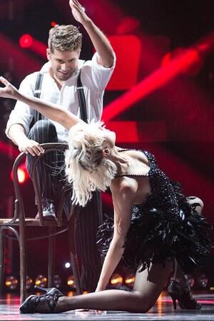Deux danseurs sur une scène. Elle porte une jupe en plumes.
