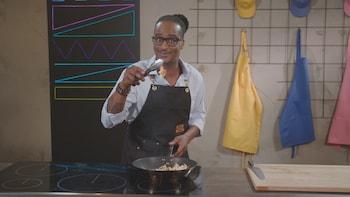 Une personne tient une crevette cuite entre les pinces de cuisson au-dessus d'une poêle.