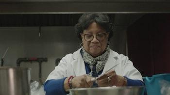Une personne coupe des oignons dans la cuisine commerciale de son magasin.