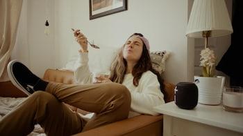 Assise dans un sofa, la personne mange de la crème glacée.