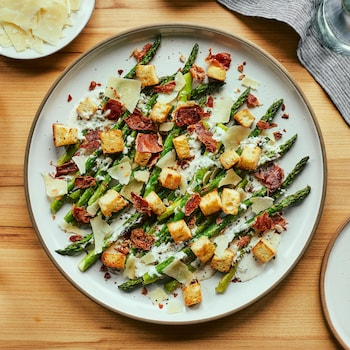 Asperges grillées servies avec de la vinaigrette César, des croûtons de pain, du parmesan et du prosciutto.