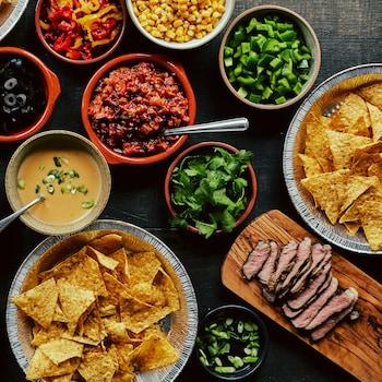 Des croustilles de maïs et des accompagnements à nachos sont servis dans plusieurs petits plats.