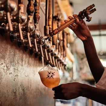 Une personne sert un verre de bière en fût.