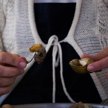 Derrière sa marmite, une femme cuisine des caricoles.