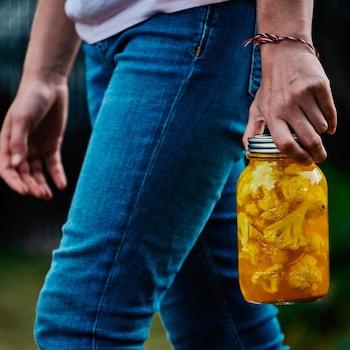 Une personne tient dans une main un bocal de choux-fleurs marinés.