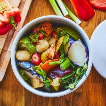 Un bol rempli de retailles de légumes est déposé sur un comptoir en bois.