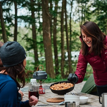 Geneviève O'Gleman dépose un plat chaud de croustade aux pommes au milieu d'une table à pique-nique où sont attablés trois convives.