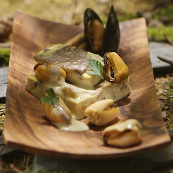 Des moules, un flanc carré au champignon sur une assiette en bois.