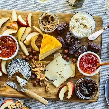 Fromages, pommes en quartier, noix et gelées sont présentés sur une planche en bois.