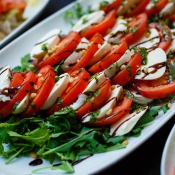 Des tranches de tomates et de bocconcini sur un lit de roquette, filets de balsamique sur une assiette blanche.