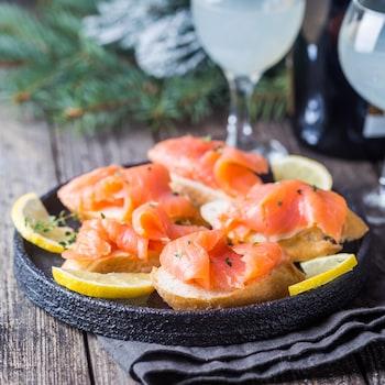 Des tranches de saumon fumé sur pain et des quarts de citron sur une assiette noire.