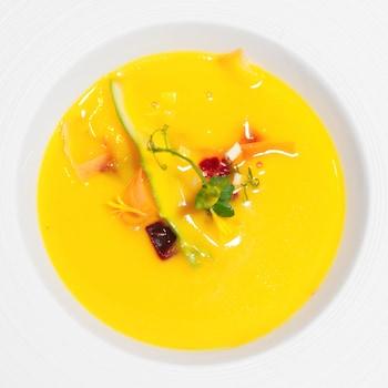 Un gaspacho jaune, des légumes sur le dessus dans un bol en porcelaine blanc.