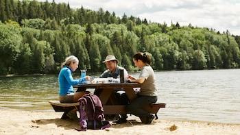 Geneviève mange une salade de couscous dans la réserve faunique Mastigouche avec des invités.