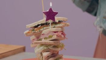 Une bougie en forme d'étoile trône sur une montage de sandwichs pas de croûtes.