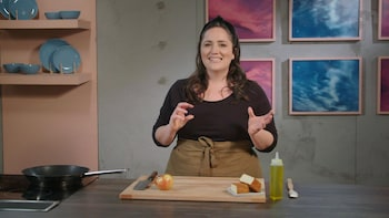 Derrière un ilot de cuisine, une personne explique comment couper une pomme pour ajouter ces morceaux dans une vinaigrette.