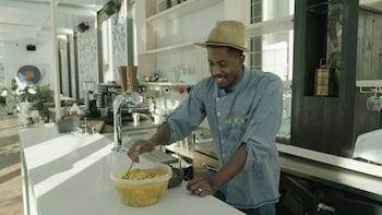 Une personne sert un bol de soupe Joumou.