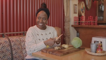 Une personne est assise à une table d'un restaurant et tranche des légumes.