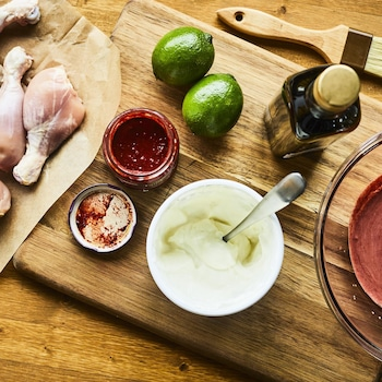 Six pilons de poulet, deux citrons verts et trois sauces ont été posés sur une planche à découper.