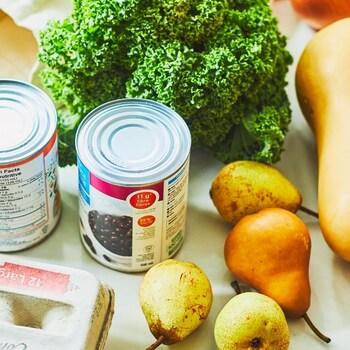 Une douzaine d'œufs, une boîte de salade de fruits en conserve, une boîte de conserve de haricots noirs, des poires, une courge et un chou frisé sont posés sur un comptoir de cuisine.