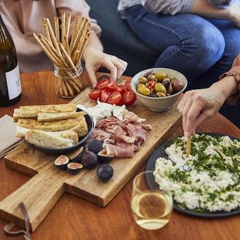 Les mains de quatre personnes autour d'une table de salon qui prennent l'apéro avec une bouteille et des verres de vin et une planche de bois avec charcuteries, pain, olives, figues, tomates ainsi qu'une assiette de fromage frais aux herbes.