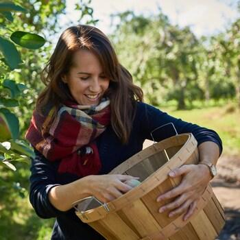 Geneviève O'Gleman dans un verger qui dépose une pomme dans un panier.