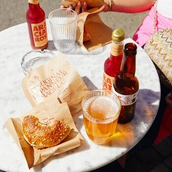 Des bagels et de la bière sur une table ensoleillée.
