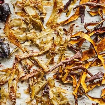 Des épluchures de pommes de terre cuites refroidissent sur une plaque.