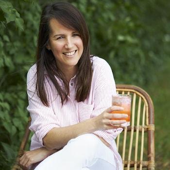 Geneviève O'Gleman assise sur une chaise en bois dans un jardin et tenant un cocktail dans sa main.