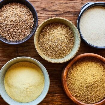 Des bols de grains de blé entier, de blé concassé, de boulgour, de semoule et de couscous.