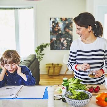 Geneviève O'Gleman prépare une salade. Elle regarde un enfant qui fait ses devoirs à côté d'elle.